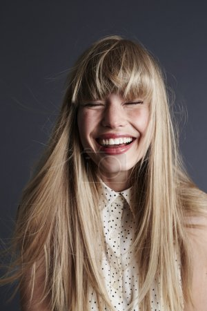 Wild haired and laughing young woman
