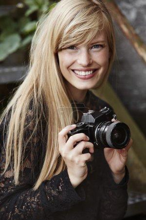 Glamorous photographer holding retro camera