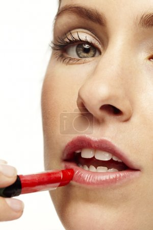 woman putting on red lipstick