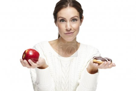 Photo for What to choose? Healthy or unhealthy. Portrait of a beautiful young woman choosing between an apple or a donut On a white background - Royalty Free Image