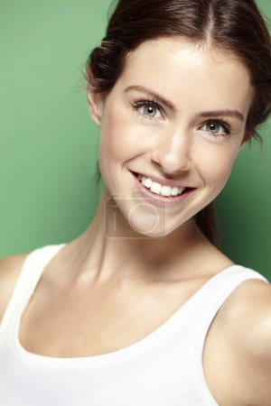 Photo for Portrait of a young woman smiling on a green background - Royalty Free Image