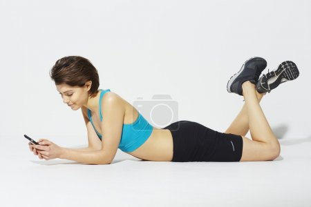 Photo for Beautiful Sporty woman using cell phone - Royalty Free Image