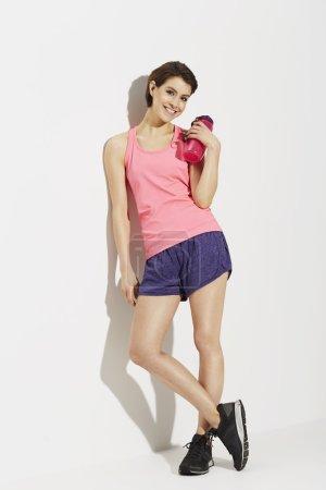 Photo pour Verticale de femme sportive retenant la bouteille dans le studio - image libre de droit