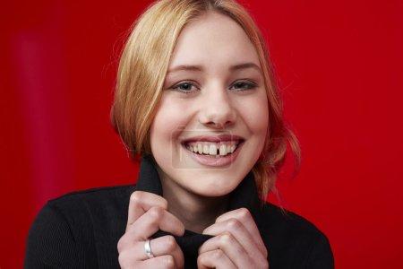 Photo pour Young woman smiling against red background - image libre de droit