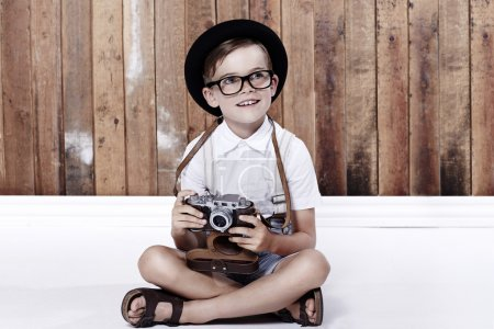 Boy sitting on floor with camera