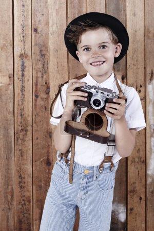 Photo pour Jeune garçon tenant vieil appareil photo, portrait - image libre de droit