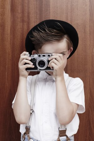 Boy taking photograph with old camera