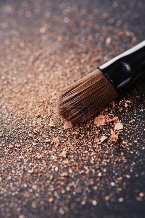 Photo pour Poudre dispersée sur fond noir à partir du pinceau de maquillage - image libre de droit