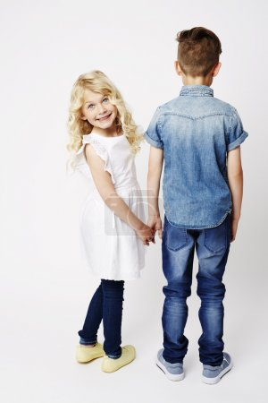 Photo for Sister turning to grin at camera with brother in studio - Royalty Free Image