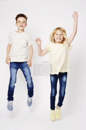 Photo for Excited brother and sister jumping with joy isolated on white - Royalty Free Image