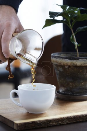 Woman pouring carafe of coffee