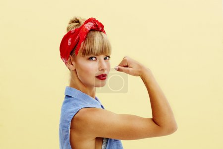Strong young blond woman flexing muscle, portrait...
