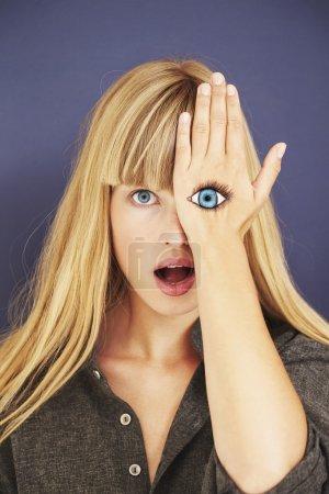 Photo pour Choqué femme blonde avec des yeux peint, portrait - image libre de droit