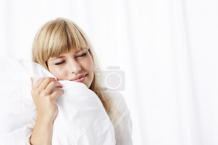 Young blond woman with duvet
