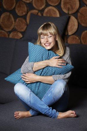 Photo pour Jeune femme riant sur canapé à la maison - image libre de droit