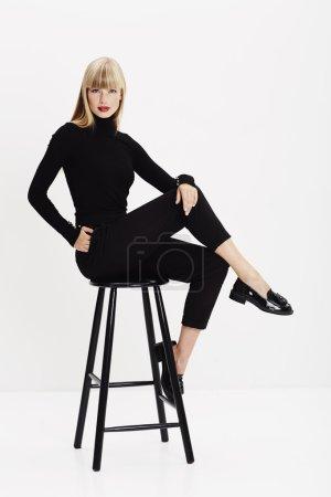 Photo for Fashion model sitting on stool in white studio - Royalty Free Image