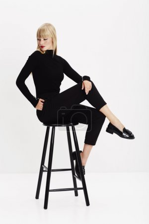 Photo for Young fashion model sitting on stool in studio - Royalty Free Image