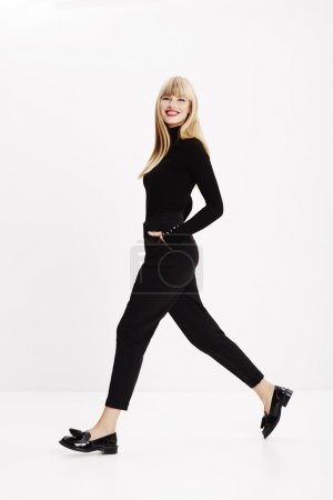 Photo for Walking young model in black fashion, studio - Royalty Free Image