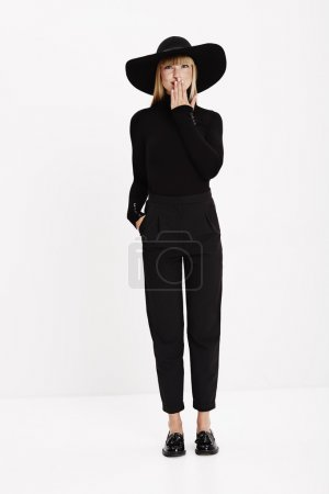 Photo for Young model in black hat and clothes, studio - Royalty Free Image