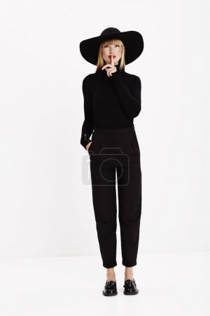 Photo for Young female model in black with finger on lips - Royalty Free Image