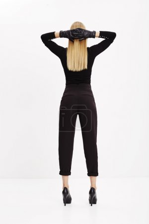 Photo for Blond woman standing in cool black clothing in studio - Royalty Free Image