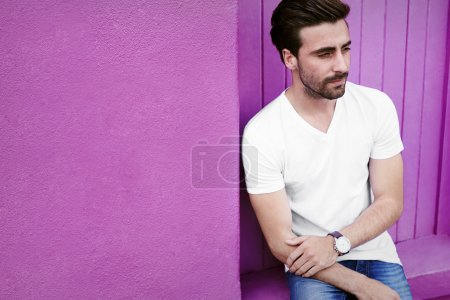 Photo for Pensive young guy against purple wall, looking away - Royalty Free Image