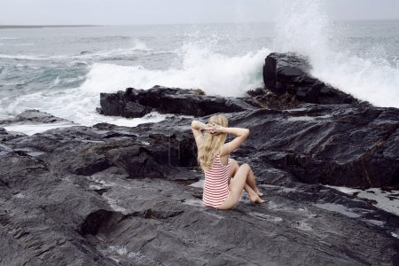 Photo for Young blond woman in swimsuit watching sea crash onto rocks - Royalty Free Image