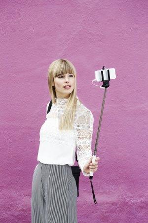 Photo pour Femme blonde et belle posant pour selfie contre rose - image libre de droit