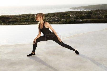 Photo pour Jeune femme Sportswear qui s'étend au bord de la piscine - image libre de droit