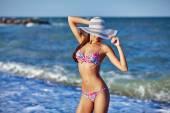 Sexy krásná žena v barevné plavky a klobouk na pobřeží moře. Exotické země cestovat a zbytek koncepce