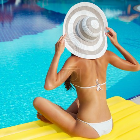 Portrait of beautiful tanned woman relaxing in swimming pool in white swimwear, hat and sunglasses. Exotic model. Creative gel polish manicure and pedicure. Hot summer day and bright sunny light.