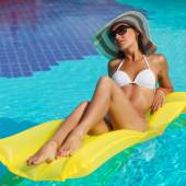 Portrét krásné opálené ženy relaxaci v bazénu v bílé plavky, čepici a brýle. Kreativní gel polský, manikúru a pedikúru. Horký letní den a jasné slunečné světlo