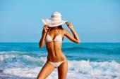 Sexy krásná žena v bílé plavky a kreativní klobouk na pobřeží moře. Západ slunce měkké světlo