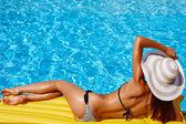 Portrét krásné opálené ženy v bikinách a klobouk v bazénu. Gelu vyleštěte červená manikúra. Horký letní den a jasné slunečné světlo