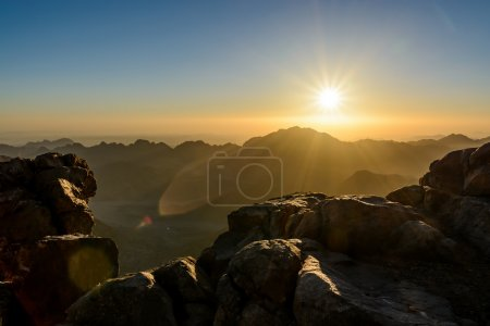 Egypt, Sinai, Mount Moses. View from road on which pilgrims climb the mountain of Moses and dawn - morning sun with rays on the sky.
