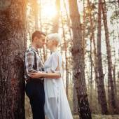 Outdoor lifestyle portrait of young couple hugging in pine forest. Sunny warm weather. Backlight and sun. Retro vintage toned image, film simulation.