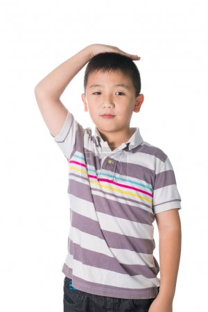 Boy growing tall and measuring himself, isolated on white backgr
