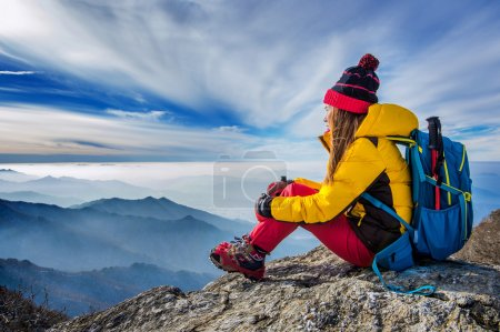Young woman sitting on the hill of high mountains.