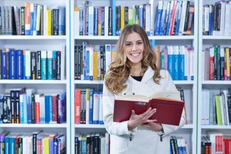 Photo pour Belle étudiante étudiant en bibliothèque - image libre de droit