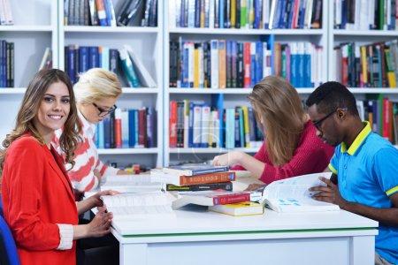 Photo pour Groupe d'étudiants apprenant dans la bibliothèque et en profiter - image libre de droit