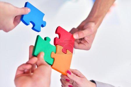 Geschäftsleute bauen Puzzle zusammen