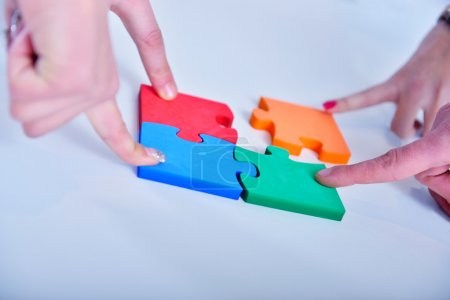 business people assembling jigsaw