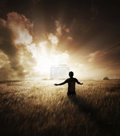 Photo pour Jeune homme aux bras écartés regardant vers un beau coucher de soleil . - image libre de droit