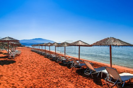 Straw umbrellas and sunbeds on a red sand beach and turquoise wa