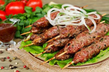 Grilled kebabs on wooden skewers and fresh vegetables