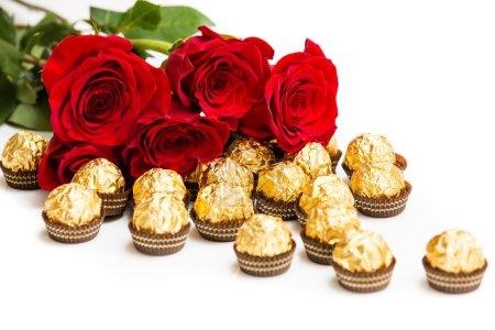 Photo pour Roses rouges et bonbons d'or - image libre de droit