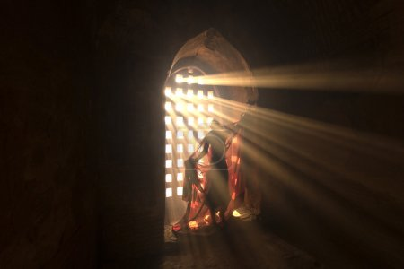 Photo for Novices are dressed with light shining through a window in the pagoda. - Royalty Free Image