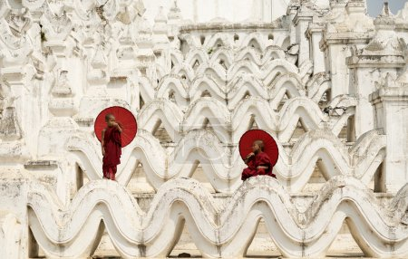 Burma,The Novice monk holding red umbrella on the pagoda