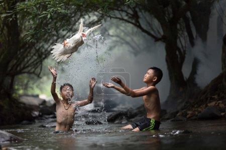 Photo pour Le garçon a jeté un canard blanc du flux. - image libre de droit