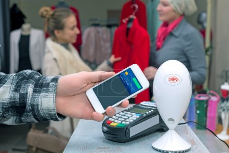 Near Field Communication - Man completing mobile Payment Woman shopping